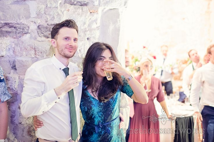 Wedding guests toast speeches with groom's home made limoncello. Photography by one thousand words wedding photographers