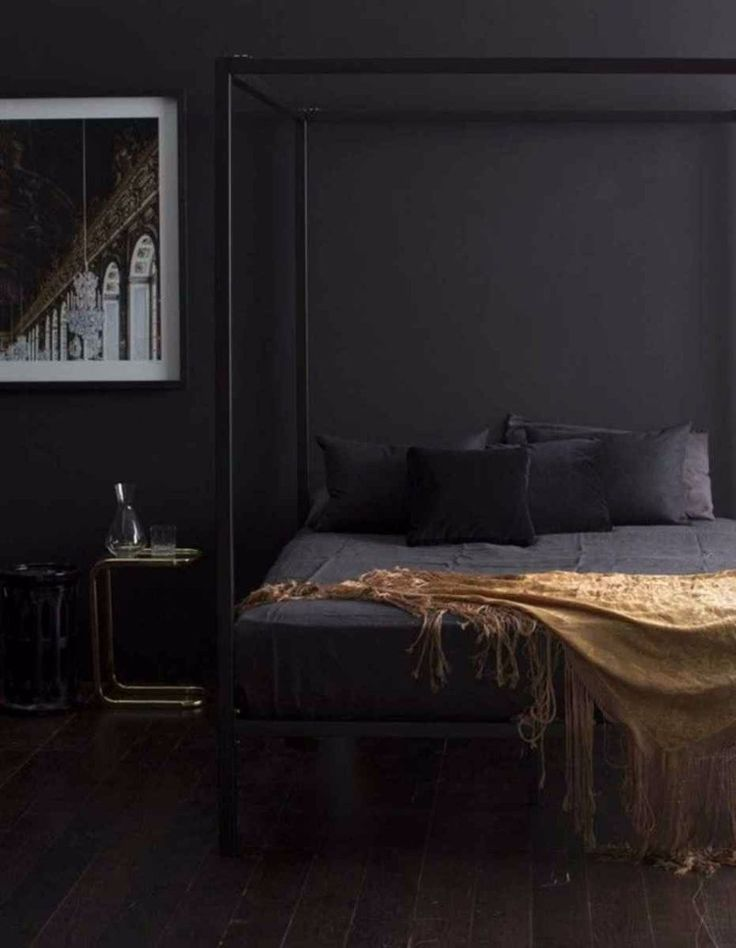 Dark and Mysterious, this dark bedroom sees a contemporary canopy bed with a golden rug that screams luxury. Very restrained, very elegant design.