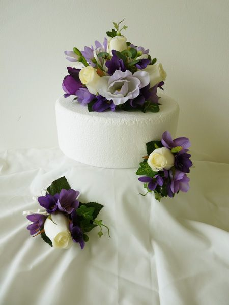 "Three piece cake set consisting of 6"" cake topper of ivory roses with purple freesia and lilac lisianthus with two matching sprays for the remaining two tiers."