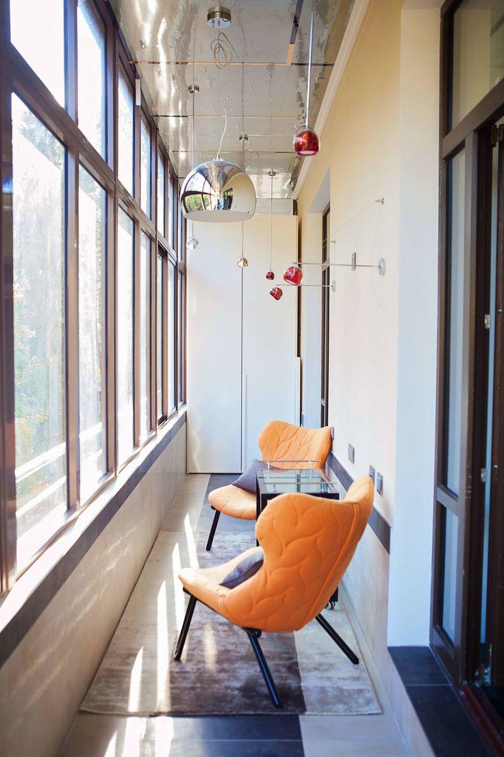 Глянцевый потолок с подвесными люстрами зрительно увеличивает площадь лоджии.