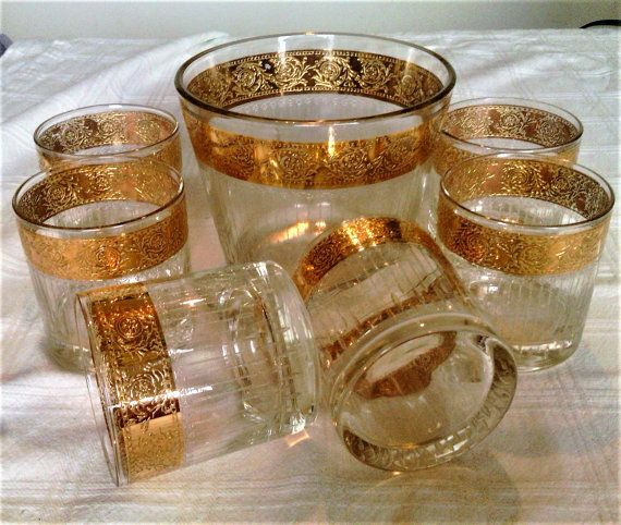 Vintage bar set consists of six low ball or rock glasses and matching ice bucket, Made by Culver in the atomic era, the pattern name is Tyrol. Decorated with 22k gold trim. The trim on the ice bucket is almost an inch tall and the glasses trim is about 3/4 of an inch. The ice bucket is about