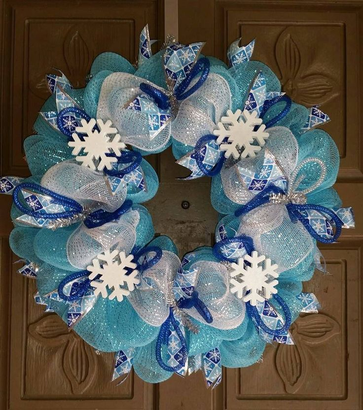 "This is a beautiful 24"" blue, white and silver deco mesh winter holiday wreath. It is made of blue, white and silver mesh and accenting snowflake ribbons and hand painted wooden glistening snowflakes."