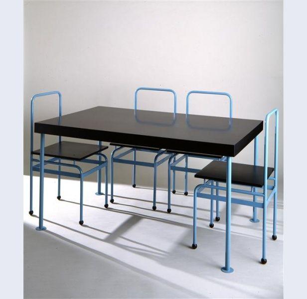 Ontwerp J.J.P. Oud [1890-1963], uitvoering Ecart International Eetkamertafel met vier stoelen Nederland (ontwerp); Parijs (Frankrijk) (uitvoering) ontwerp 1927 replica 1979 tafel: hoogte 75 cm; breedte 90 cm; diepte 140 cm stoel: hoogte 90,7 cm; breedte 42,3 cm; diepte 45 cm blauw gekleurd metaal, hout en rubber Gemeentemuseum Den Haag: 1033594