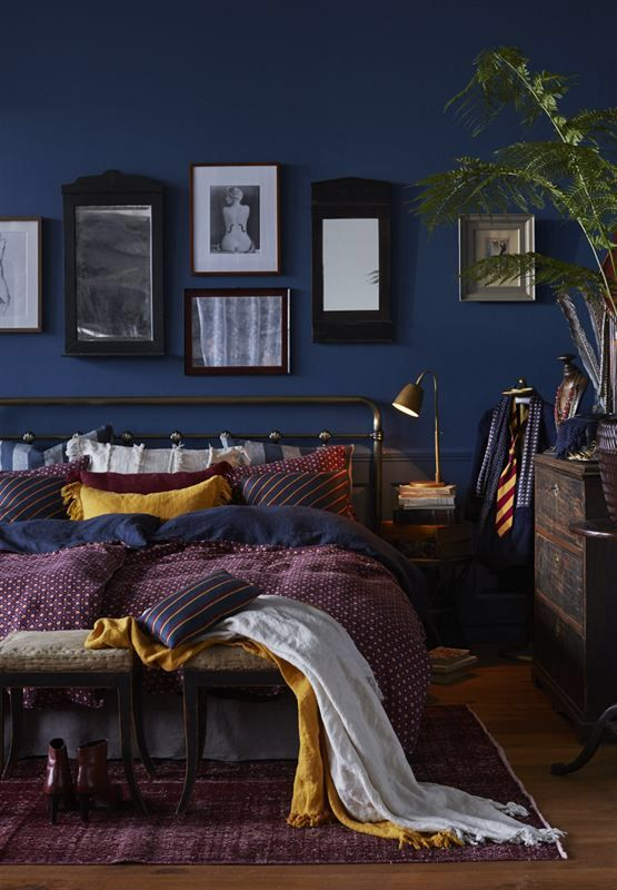 Blue wall black frames dark bedroom bed
