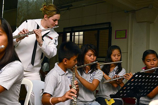 Musician 3rd Class Christa Vernon plays the flute with students during a U.S. 7th Fleet Band visit to the Philippine Women's University. The band is embarked aboard the U.S. 7th Fleet flagship USS Blue Ridge (LCC 19), on a port visit to Manila.