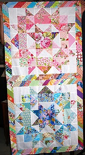 Swoon blocks with scrappy sashing.  large print in center of star defines coordinating fabrics with the out ring of star. plan background. Darker fabrics for block borders cut on diagonal.  Still want to know what a Swoon Block is????