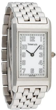 Ladies' stainless steel 38mm Tiffany & Co. Quartz Watch with smooth bezel, white dial, silver-tone Arabic numerical hour markers, push/pull crown, calendar aperture at 3 o'clock position, stainless steel bracelet and double deployant closure. Includes box.