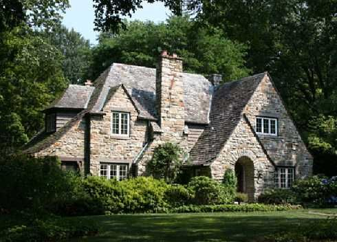 Located outside of Philadelphia, Pennsylvania, USA, this lovely  Tudor Revival  home features numerous gables and dormers,  as well as a large chimney that extends upward along the  outer  wall  of  the front  facade  --  a  common architectural design element of English period revival styles in North America at that time.