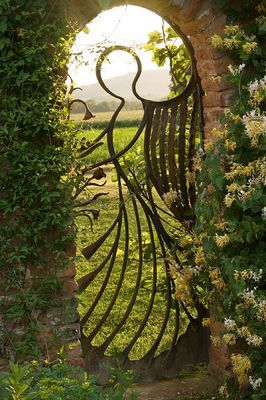 BIRTSMORTON COURT, WORCESTERSHIRE: THE ANGEL GATE IN THE WALLED GARDEN LOOKING OVER THE MALVERN HILLS