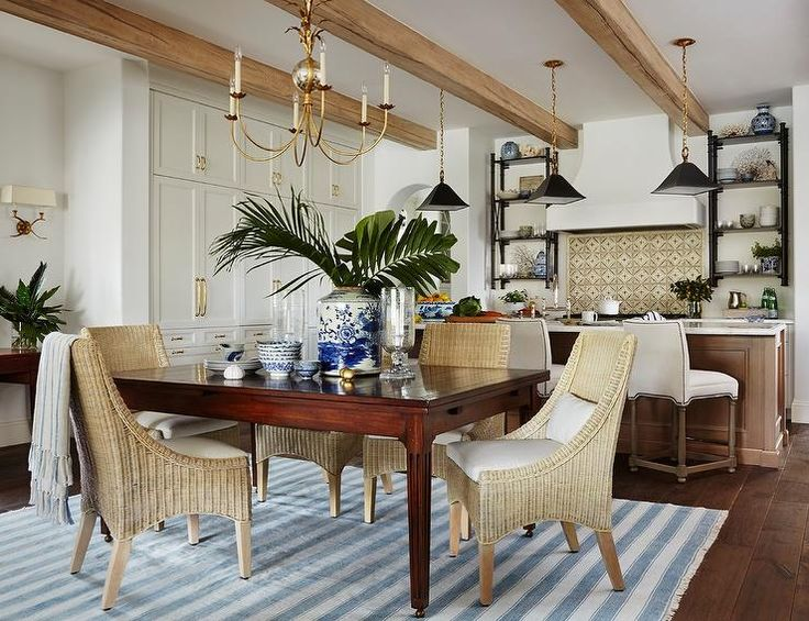 A brass leaves chandelier illuminates a cherry stained dining table lined with light wicker dining chairs placed atop a light blue striped rug.