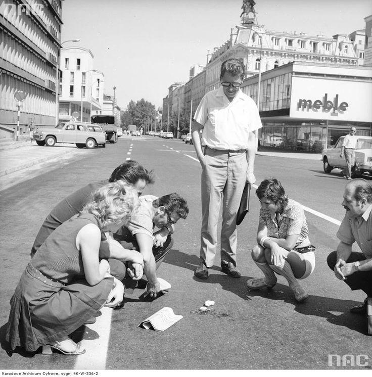 Grupa kobiet i mężczyzn przy ulicy Przeskok w Warszawie rozbija jajko na rozgrzanym asfalcie aby sprawdzić temperaturę nawierzchni, 1967-1970