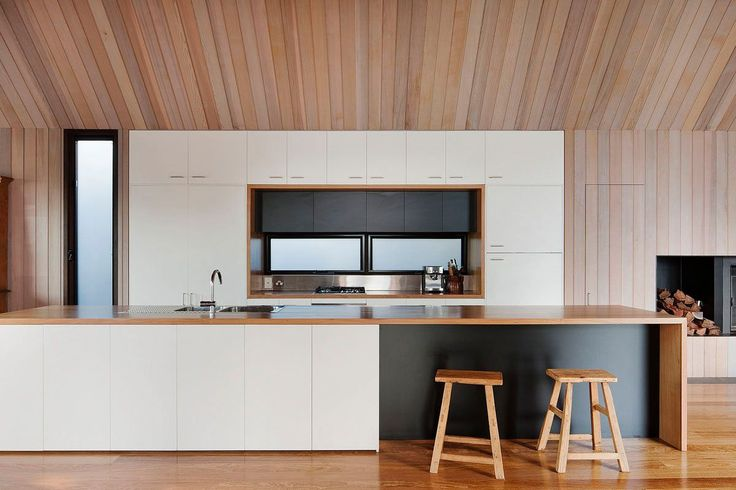 Photo by Shannon McGrath The Seaview House, by Jackson Clements Burrows, features a pavilion-like kitchen with simple white cabinets, wooden countertops, and an island that has a black panel underneath the bar. Vertical wood boards skim the walls and continue up the pitched ceiling adding warmth to the open space.