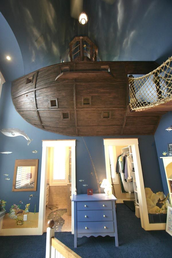Unique Bedroom Design by Steve Kuhl Featuring a Pirate Ship: upstairs a hole in the wall takes you sliding down a slide to a comfortable pillow located in the actual bedroom. A wooden rope bridge is used to access the ship, where the crow's nest reigns, alongside a second bed, for guests.