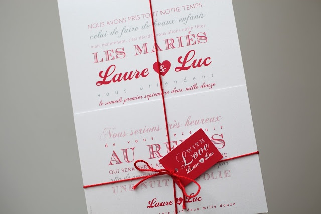 Letterpress wedding invitations tied with red string bow with a red tag to finish.
