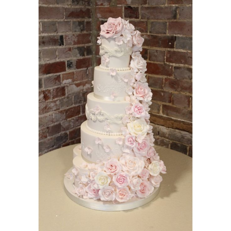 Five tier ivory and blush wedding cake with large cascade of sugar roses