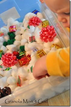 Christmas sensory bin: cotton balls, small gifts, bows, red and green pom poms, bells