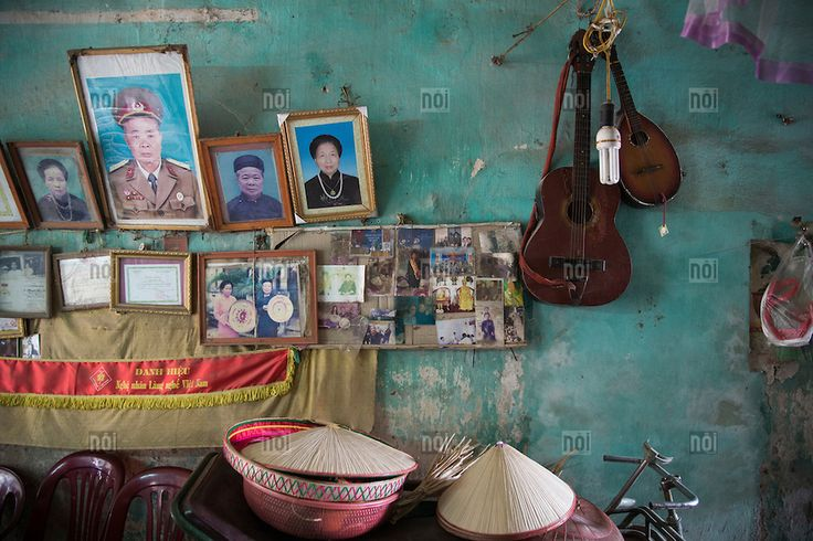 [photo by Francis Roux] A wall devoted to family photos and meaningful items in a home of Chuong Village, Ha Tay Province, Vietnam