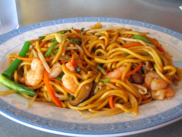 Shrimp and Vegetable Lo Mein  1 tsp finely grated ginger  2 Tbspn rice vinegar  3 Tbspn soy sauce  ¼ tsp toasted sesame oil  ½c chicken broth (preferably low-sodium)  2 tsp cornstarch  ½ tsp of chili garlic sauce  ---  1 carrot shredded,  1 red bell pepper julienne,  1 yellow bell pepper julienne,  1 c snow peas ends and strings removed, julienne same width as bell peppers,  3 scallions sliced,  1 c fresh bean sprouts,  2 Tbspn vegetable oil,  1 lb shrimp peeled and de-veined,  Juice from ½…