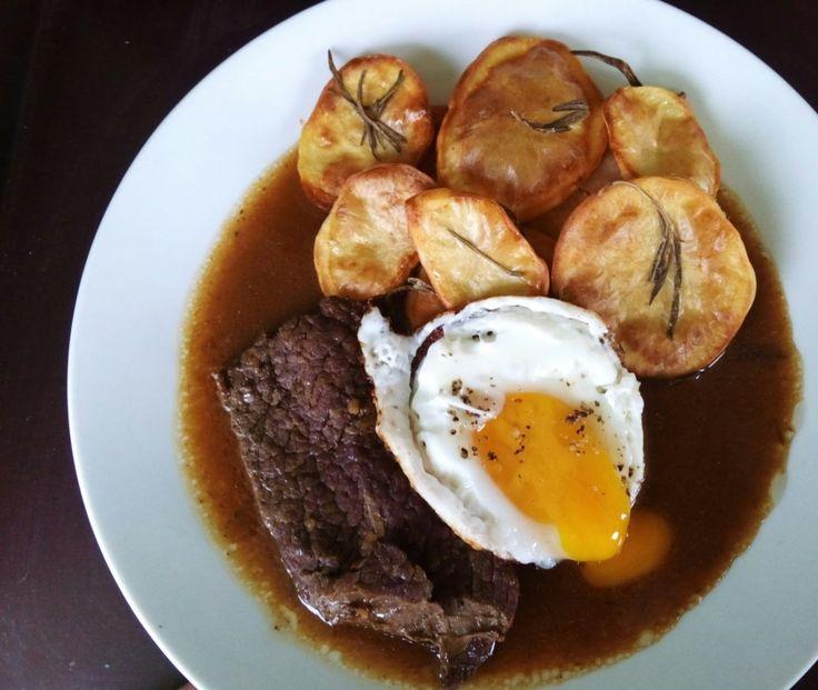 Hovězí plátek se silnou omáčkou, pečenými rozmarýnovými brambory a volským okem