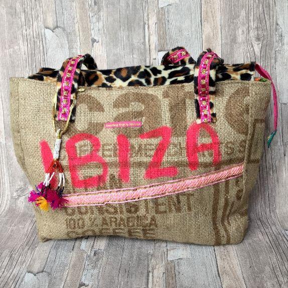 Super unieke grote shopper van jute. De tas is gemaakt van gebruikte koffiezakken en is met de hand beschilderd met knalroze verf en voorzien van verschillende soorten band en andere leuke accessoires. Gebruik deze tas als strandtas, sporttas en je je steelt beslist de show!