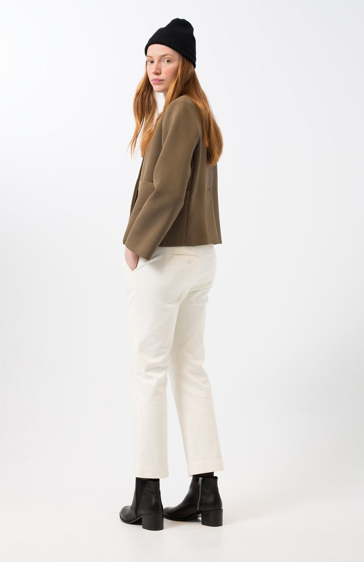 Nikole khaki light jacket. Khaki, neoprene, straight cut blazer. Large patch pockets. Round neckline. Front hidden buttons closure. Back vent at the hem. Regular fit and short.