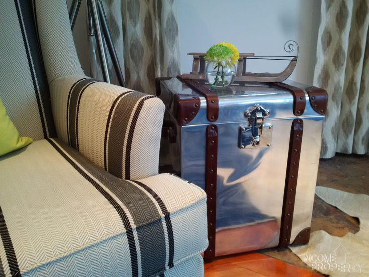 A nod to the #vacation theme of #incomeproperty #season11 with this stunning #stainlesssteel #suitcase. The complimentary patterns of the rug, curtains and wingback make this living room a renters #skihaven #incomepropertydesign #scottmcgillivray #textiles #complimentary @hgtv @scottmcg