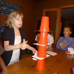 Stack 6 plastic cups with index cards between them. Then pull the cards out to make the cups all stack together