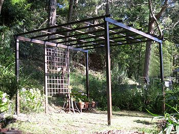 A steel hoop arbor and a pergola frame draped with canvas for Metal frame pergola designs