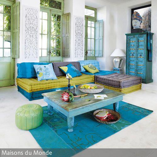 Blaue, gelbe und grüne Möbel, angestrichen oder dekoriert mit Ethnomustern erinnern an eine orientalische Einrichtung. Die niedrigen Sitzpolster mit dem  …