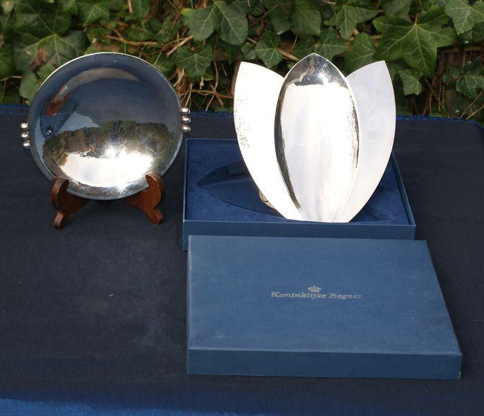 Twee schalen Paul de Vries en Quist Nederland en Duitsland 2e helft 20e eeuw en 1e helft 20e eeuw  Schaal 'Tulip' in de vorm van een tulp ontworpen door zilversmid Paul de Vries (1958) van atelier ''Passi'' uit Schoonhoven. Geproduceerd bij de Koninklijke Begeer en is in uitstekende conditie. De schaal is 24 x 21 cm en zit nog in de originele verpakking. De verpakking is 28 x 25 cm en bijna 45 cm hoog. Gehamerde schaal van Quist doorsnee 19 cm Nederland en Duitsland minimale gebruikssporen…