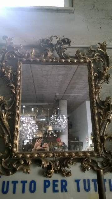 Specchio con cornice a ricciolo.