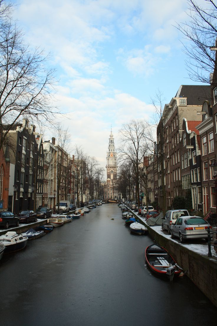 Winter panorama of Amsterdam city in Netherlands with frozen canal