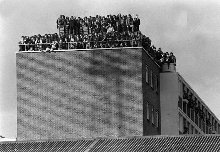 14th February 1972, Fans crowd the roof of a block of flats overlooking West Ham's Upton Park pitch as the Hammers win their FA Cup replay v Hereford 3-1