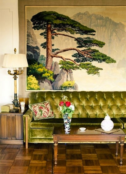 Vintage space love the buttonback upholstered couch in green velvet and massive treescape print behind sofa