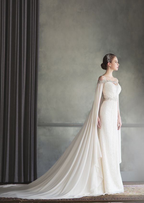 How beautiful is this Bonheur Sposa gown featuring an unique off-the-shoulder jeweled neckline and a stylish cape!