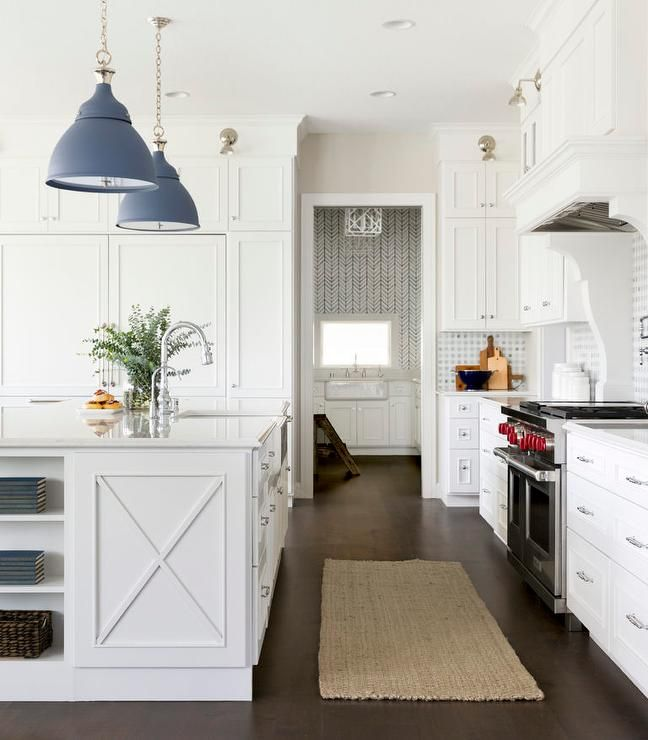 Fitted with cookbook shelves and a gorgeous x-trim, a white center island boasts a farmhouse sink with a polished nickel gooseneck faucet mounted to a white quartz countertop illuminated by blue light pendants.