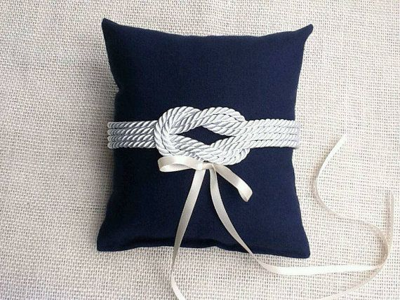 Perfect for your Nautical theme wedding. This pillow is made of navy blue canvas, and decorated with a nautical knot and a satin ribbon to tie