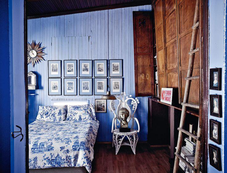 El dormitorio principal está pintado en azul wegdwood y reúne la colección de obra gráfica del dueño. La ropa de cama es un toile de jouy azul y blanco. Los libros y las revistas invaden las estanterías. Junto a la cama, silla inglesa de caña estilo balneario.