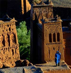A man dressed in traditional Berber robe stands on top of the Ait Ben Haddou fortress near Ouarzazat, Morocco, December 31, 2002. [© AP Images]