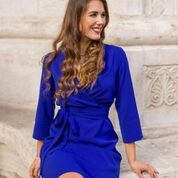 A knee-long flared cocktail/smartcasual dress with a wrap neckline and material belt by CIRIANA.