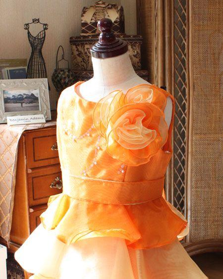 """ピアノの発表会やお子様の演奏会、結婚式の参列で""""子供用フォーマルドレスやパーティードレス""""をお探しのお客様に  オススメする""""オレンジとイエローカラーのティアードスカートドレス""""です。     ローカルの発表会にオススメの110cmから140cmまでの子供用ドレスです。  0026 line Dressをご紹介!  シンプルなラウンドネックのドレスです。胸元にはポイントデザインとしてオレンジとイエローを交えてデコルテされたコサージュをデザイン。お子様の上半身とスカートバランスを整える""""ウェスト ベルト""""を採用したデザインです。後ろのウェストで結んで""""リボンに表現するデザイン""""です。     オレンジとイエローカラーのコンビネーションデザイン!  ティアードスカートを表現。配色とフリル感が可愛らしいスカートです。結婚式や発表会などのフォーマルなシーンにぴったりなジュニアサイズドレスですね。     110cm、120cm、130cm、140cmとレンタルが可能です。…"""