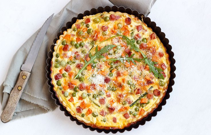 Swiss cheese and ham combine in a classic quiche filling, packed with fresh spring vegetables—a meal the whole family will love! | eatwell101.com