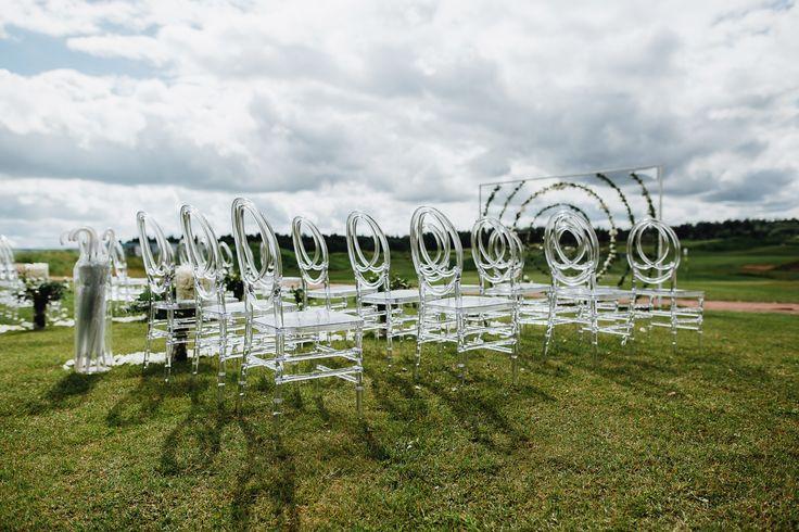 Легкая и необычная арка, в виде стеклянной стены, украшенная зеленью по кругу, словно парила в невесомости, гармонично вписываясь в панораму загородной местности. Подчеркивали воздушность оформления прозрачные стулья с округлой спинкой, а проход был украшен пряной зеленью в стеклянных вазах. Читайте историю об этой свадьбы на http://www.wedkitchen.ru/svadba-nasti-i-kosti
