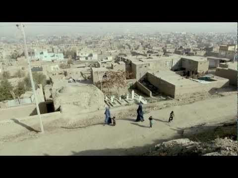 "REEL - UNREEL.  Francis Alÿs. Kabul, Afghanistan 2011 In collaboration with Julien Devaux and Ajmal Maiwandi. The film derives from Alÿs' interest in children's street games, such as the art of rolling a wheel with a stick, which he witnessed in Bamiyan and Kabul. Since the object being rolled around the undulating streets of Kabul's old town is a spool of film, ""real"" turns into ""reel."""