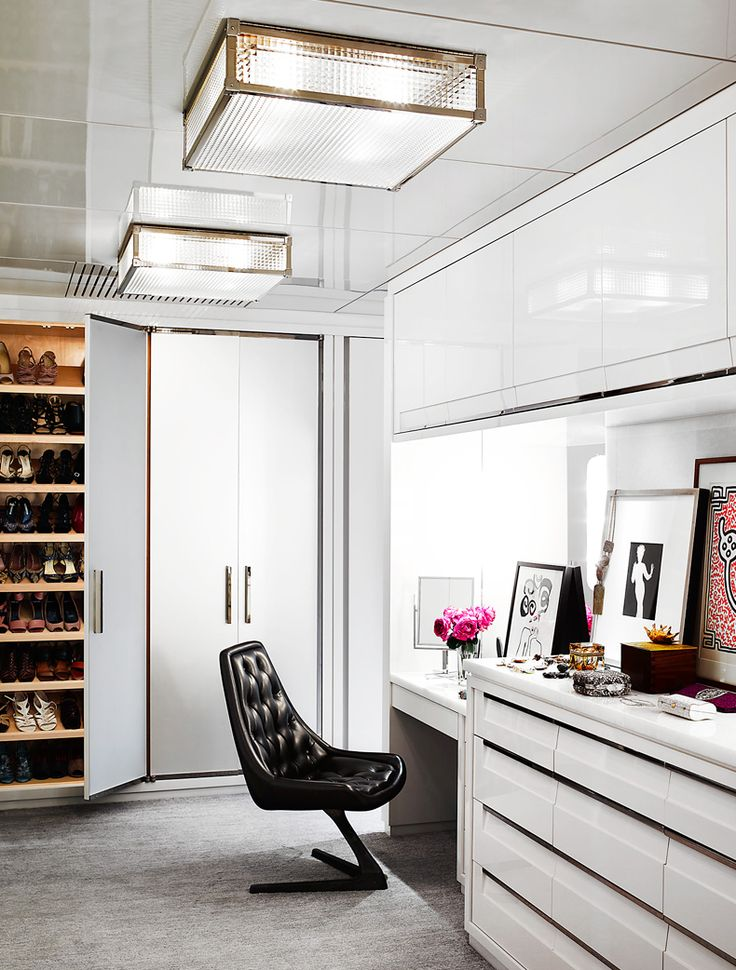 Walk in closet with crisp whites, organizational shelves, and a black leather chair