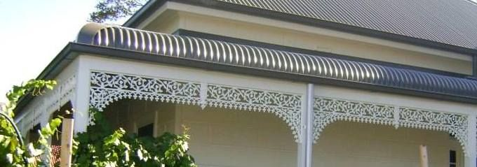 Grey Colorbond roof; white lace fretwork.