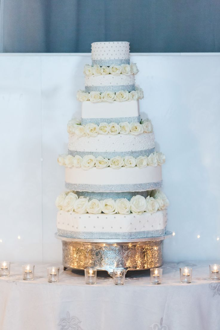 Their luxurious 6 tier wedding cake - white roses in between each tier. http://www.fusion-events.ca/