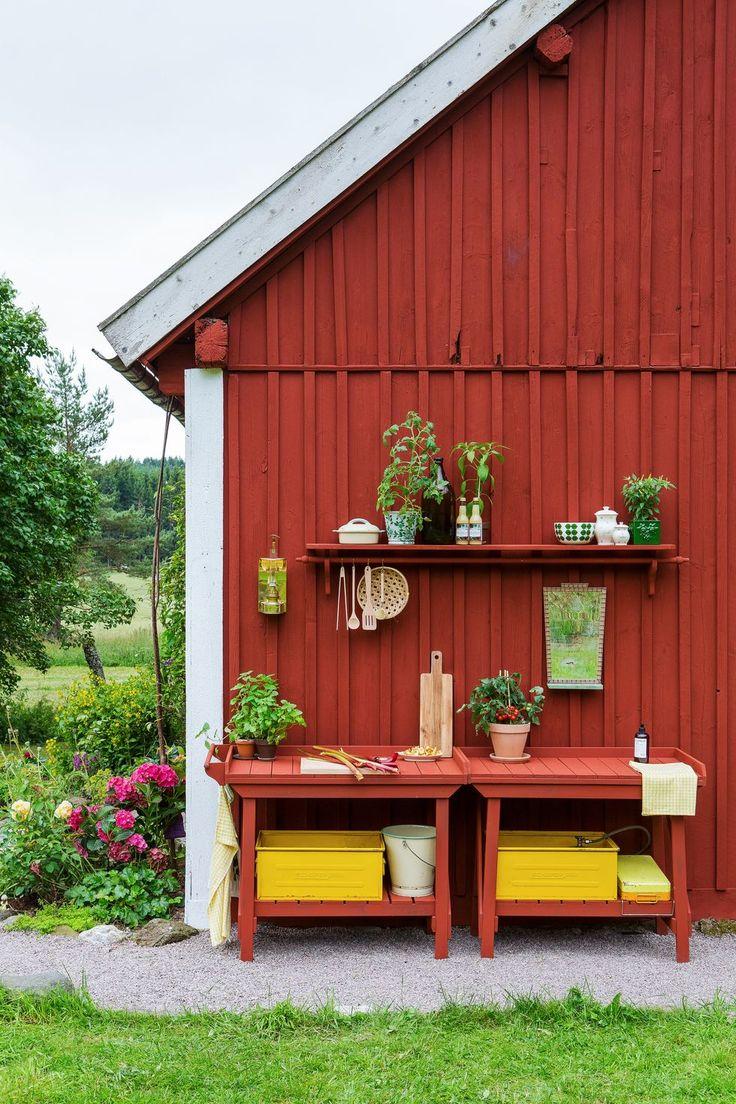 Invid huset står två arbetsbänkar som är målade i fasadens färg.