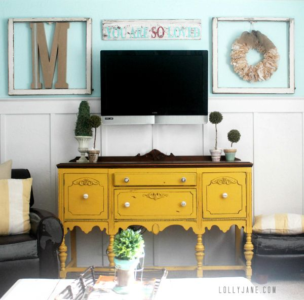 How to decorate around a tv, hang frames on either side and a sign across the top to balance it out.