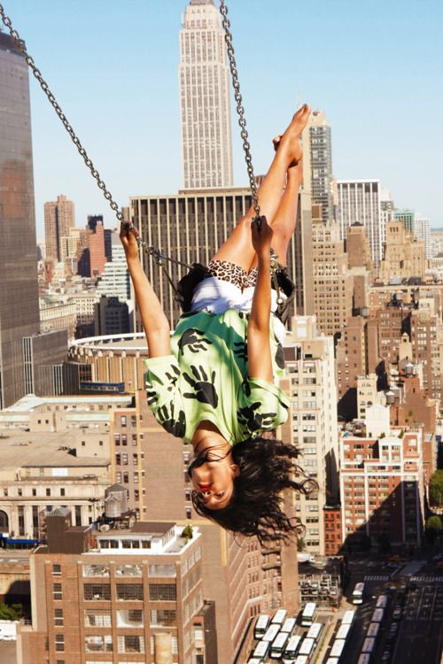 NYC. M.I.A. on a swing flying over Manhattan. // By Ryan McGinley